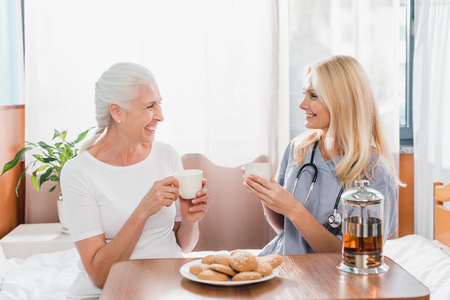 nurse and patient drinking tea and smiling each other in hospital Stock Photo