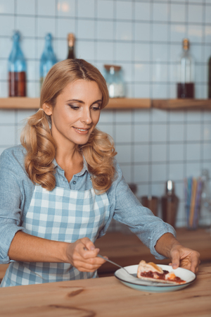 smiling waitress in apron putting piece of pie on plate Banco de Imagens