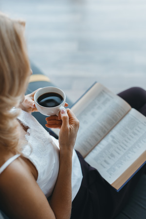 cropped shot of blonde woman drinking coffee and reading book 免版税图像