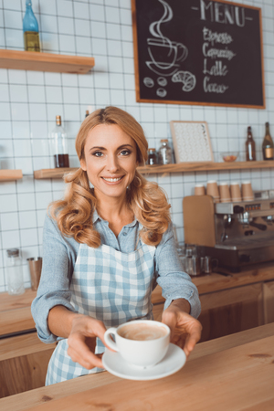 beautiful middle aged waitress holding cup of coffee and smiling at camera Foto de archivo