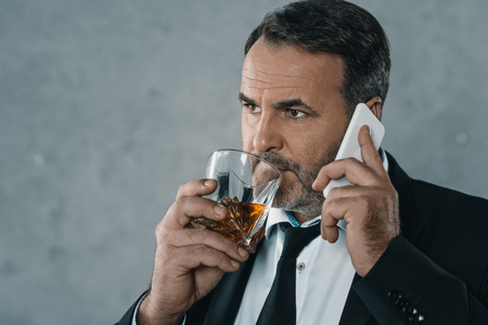 mature businessman talking by phone while drinking whiskey Banque d'images