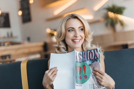 beautiful smiling mature woman reading fashion magazine and looking away in cafe