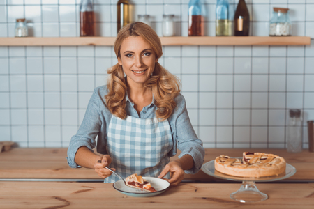 beautiful middle aged cafe owner in apron holding piece of pie on plate and smiling at camera Foto de archivo - 102321893