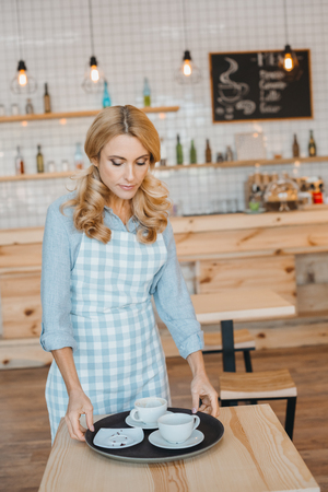 middle aged waitress in apron holding tray with empty cups and saucers Foto de archivo - 102326681