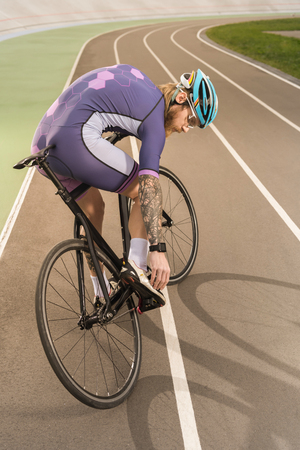 cyclist in sportswear and helmet checking shoe on cycle race track