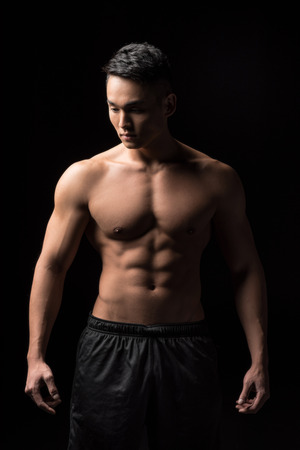young shirtless muscular asian man looking down isolated on black