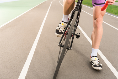 partial view of cyclist riding bicycle on cycle race track