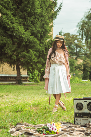 beautiful young woman in straw hat looking down while standing on grass in park