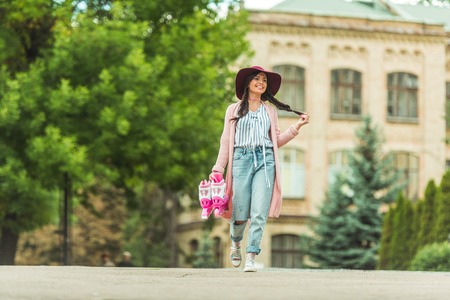 low angle view of happy stylish girl in hat holding roller skates and walking in park