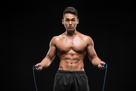 young muscular asian man standing with skipping rope isolated on black  Reklamní fotografie