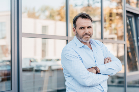 mature businessman with crossed arms looking at camera outdoors