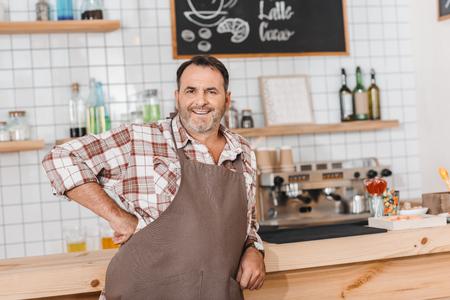 handsome mature bartender leaning on bar counter 写真素材
