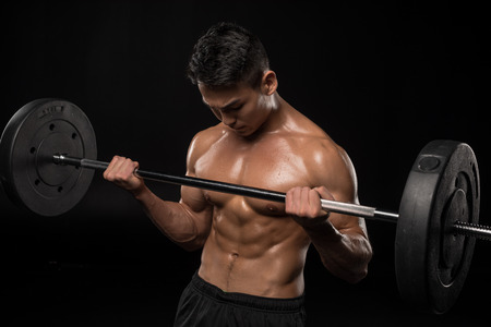 muscular asian shirtless man lifting barbell isolated on black