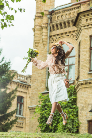 beautiful happy girl holding bouquet of flowers and jumping outside  Stockfoto