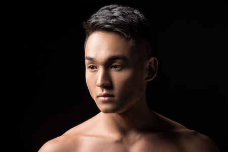 portrait of handsome young asian man looking away isolated on black