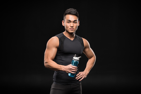 athletic young asian sportsman holding sports bottle and looking at camera isolated on black
