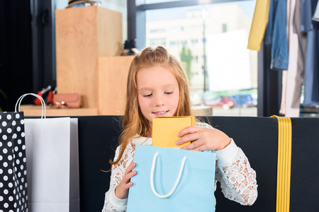 child with shopping bag sitting on sofa in boutique after shopping Banco de Imagens