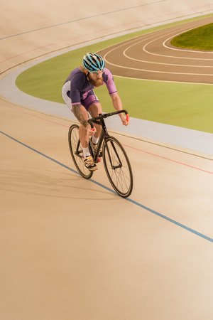 young cyclist in helmet training on cycle race track