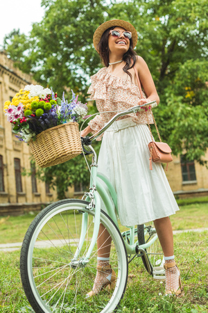 low angle view of happy stylish girl in vintage dress standing with bicycle and looking away  Stock Photo