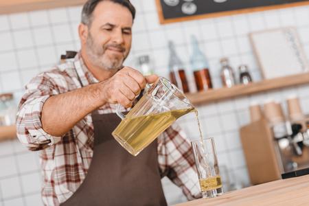 happy mature bartender pouring apple juice in glass Foto de archivo