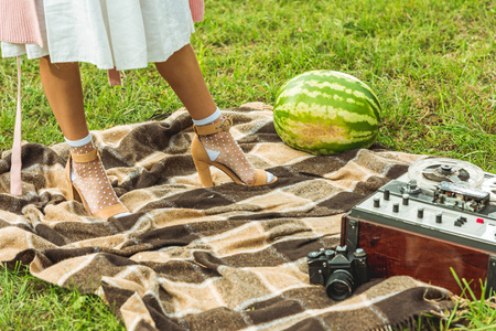 cropped shot of young woman standing on plaid with whole watermelon and tape recorder 版權商用圖片