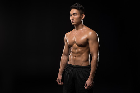 young shirtless muscular asian man looking away isolated on black Stockfoto