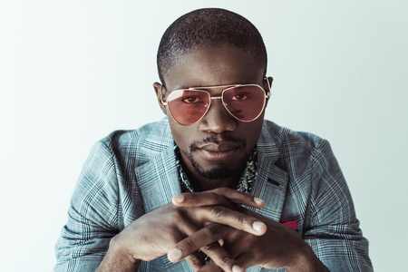 Portrait of handsome african american man in stylish clothes and sunglasses, looking at camera, isolated on grey