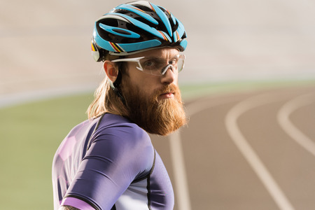 portrait of young cyclist in helmet and goggles looking at camera