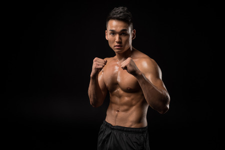 shirtless asian sportsman boxing and looking at camera isolated on black Stockfoto