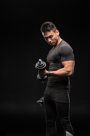 muscular asian man training with dumbbells isolated on black