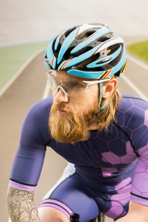 portrait of pensive cyclist in helmet and goggles looking away
