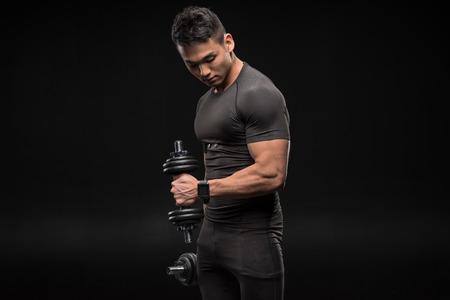 Apuesto joven asiático en hombre asiático haciendo ejercicio con pesas aislado en negro