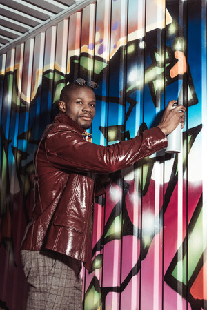 Handsome african american man in stylish clothes painting grafitti on wall with spray paint and looking at camera