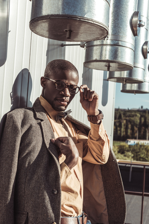 Handsome african american man in tweed jacket and eyeglasses leaning on wall and looking at camera