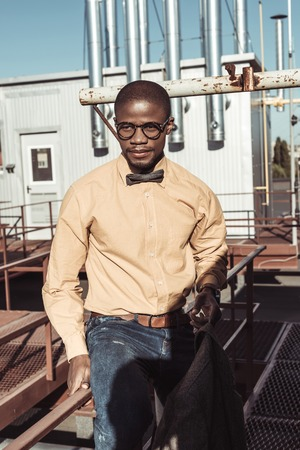 Stylish african american man wearing glasses and bowtie, sitting on guardrails and looking aside
