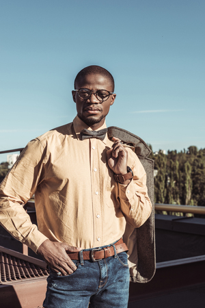 Stylish african american man in glasses and bowtie posing with jacket on his shoulder
