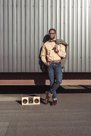 Handsome african american man with jacket on his shoulder and boombox on floor