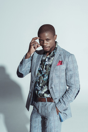 Attractive african american man in stylish suit posing with hand in pocket and looking at camera
