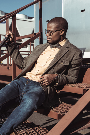 Fashionable african american man in tweed jacket and glasses, sitting on metal stairs