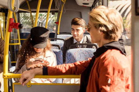 group of young people riding in public transport