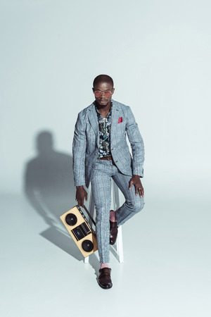 Handsome african american man in a suit and sunglasses, sitting on a bar stool and holding boombox Banque d'images - 102348531