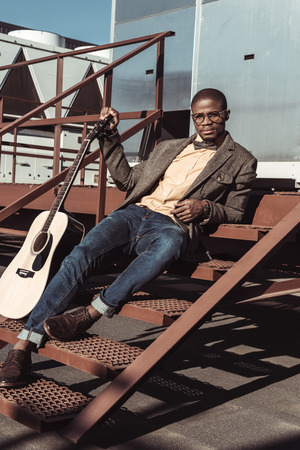 Handsome african american man sitting on metal stairs and holding an acoustic guitar
