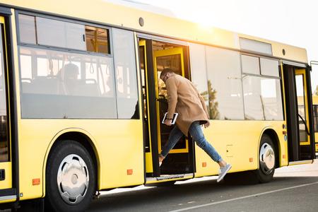 Vue pleine longueur du jeune homme tenant une tablette numérique et entrant dans le bus