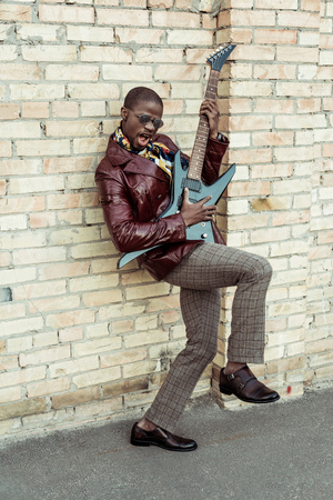 Handsome african american man in stylish clothes and sunglasses pretending to play an electrical guitar