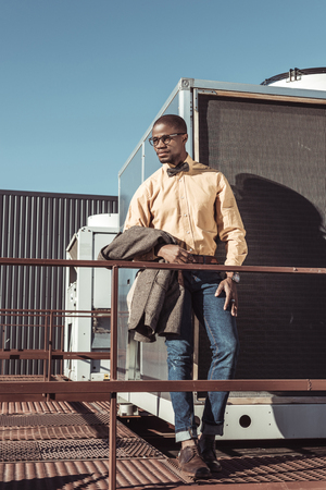 Handsome african american man holding a jacket and posing in urban enviroment
