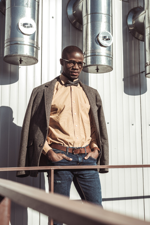 Attractive african american man wearing tweed jacket and bowtie, posing with hands in pockets and looking at camera