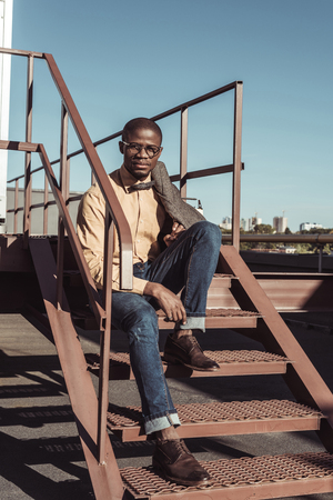 Handsome african american man sitting on metal stairs and looking at camera Stock Photo