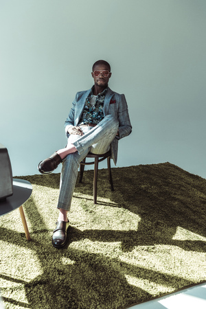 Handsome african american man in stylish suit and sunglasses, sitting on wooden chair with legs crossed and looking at camera