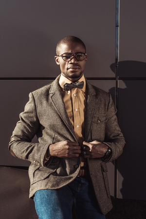Handsome african american man in formal wear and eyeglasses, buttoning up jacket