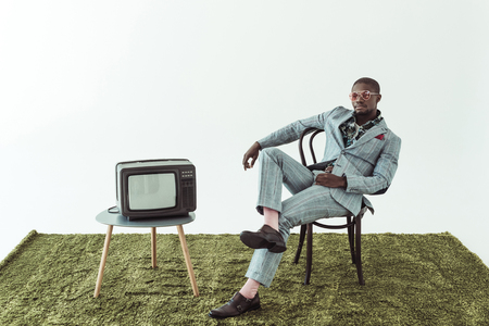 Handsome african american man in suit sitting on a wooden chair near a retro television